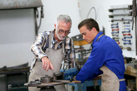 locksmith: Young man in ironworks training with professional teacher
