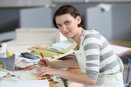Young woman painter sitting at working table photo
