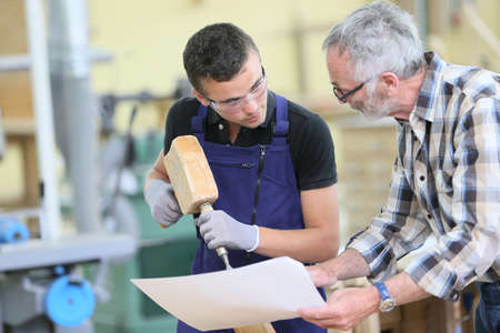 apprentice: Young apprentice with teacher working on piece of wood Stock Photo