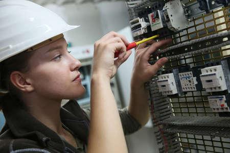 circuito electrico: Mujer joven en la formación profesional de la creación de circuitos eléctricos Foto de archivo