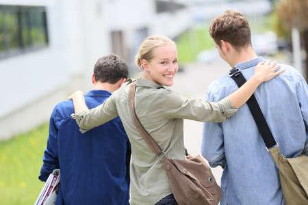 young students: Los jóvenes estudiantes que caminan edificio del campus fuera