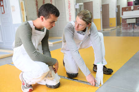 knelt: Craftsman showing apprentice how to install plastic flooring Stock Photo