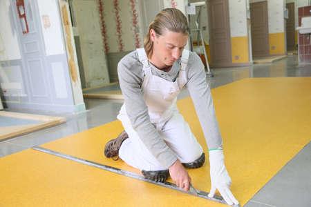 knelt: Craftsman installing plastic flooring Stock Photo
