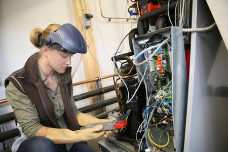 apprentice: Young woman with protective mask controlling electrical intensity