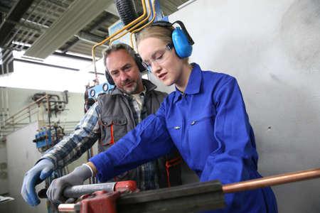 プロの配管工になるトレーニングで若い女性