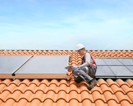 installations: Man on roof top checking on solar panel installation
