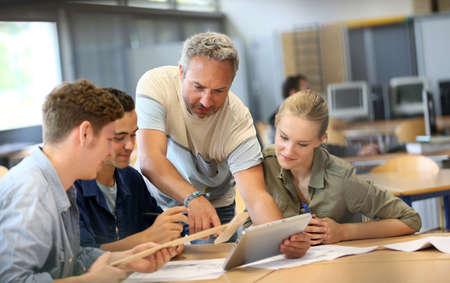 Leraar met groep studenten werken aan digitale tablet