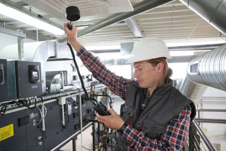 Technician controlling air quality of heating equipment photo