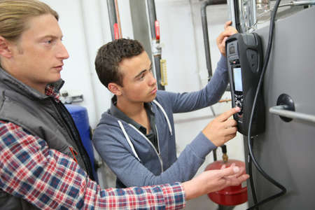 Young man in professional training measuring heat pump temperature Stockfoto