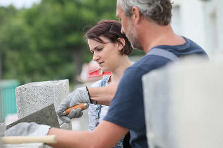 trainee: Mason with trainee in construction, building wall