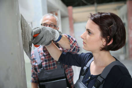 apprentice: Young apprentice with professional plasterer Stock Photo