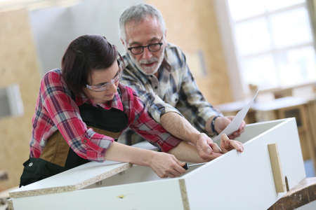 Young woman with senior craftsman in carpentry class 스톡 콘텐츠