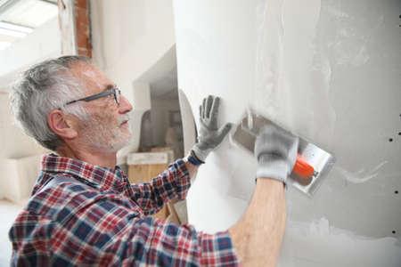 plasterer: Senior plasterer working on new construction wall