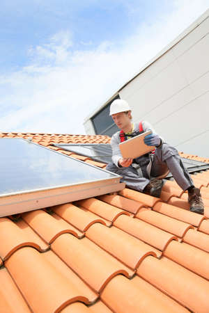 solar roof: Man on roof top checking on solar panel installation