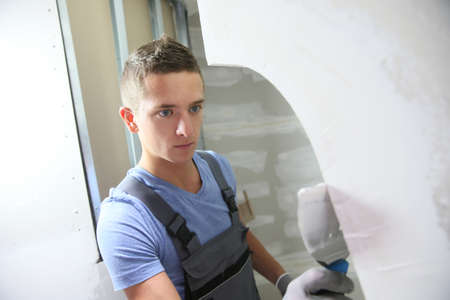 apprentice: Young plasterer working on indoor wall Stock Photo