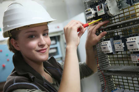 ingenieria elÉctrica: Mujer joven en la formación profesional de la creación de circuitos eléctricos Foto de archivo