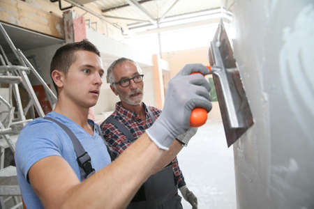 plasterer: Young apprentice with professional plasterer Stock Photo