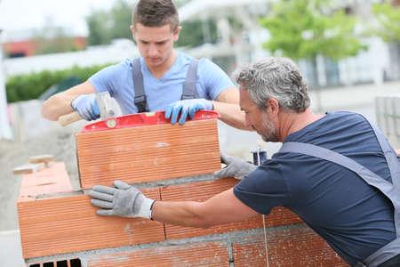 Mason met stagiair in de bouw, de bouw van de muur