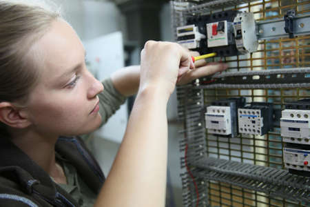 engineering: Young woman in professional training setting up electrical circuit