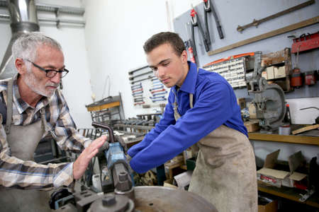 ironworks: Young man in ironworks training with professional teacher