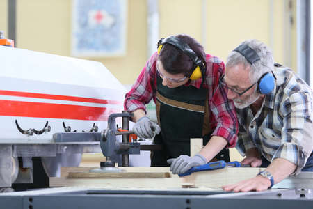 sawing: Young trainee in carpentry using sawing machine Stock Photo