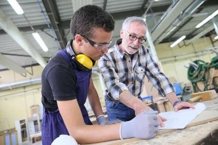 Carpenter with apprentice in training period Archivio Fotografico