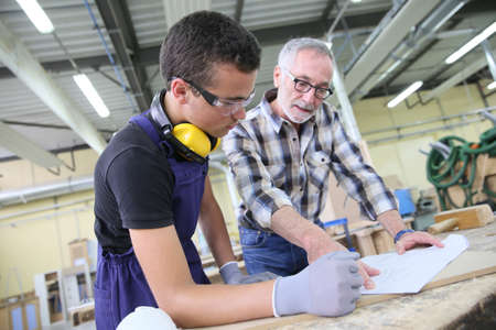 Carpenter with apprentice in training period Stockfoto