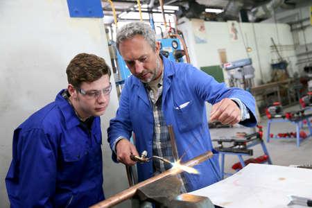 Leraar met studenten in de metallurgie werkplaats Stockfoto
