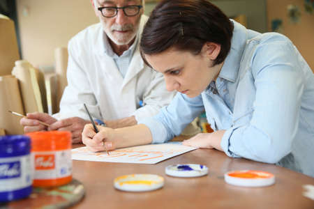 Young woman at school studying decorative painting