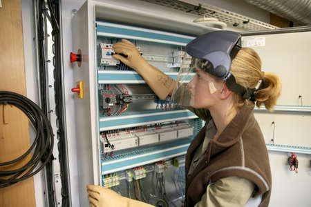 electrical system: Young woman checking electrical system of heating room Stock Photo