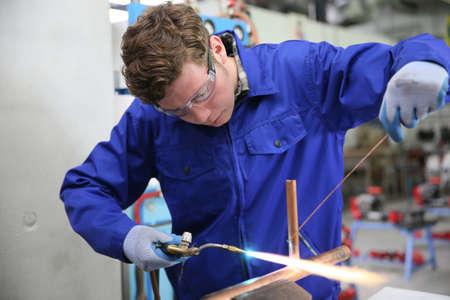 cobre: estudiante en la formación profesional de plomería, trabajando en el cobre Foto de archivo