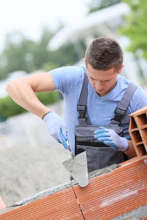 constructor: Capa de ladrillo joven que trabaja al aire libre en la construcción de paredes de ladrillo