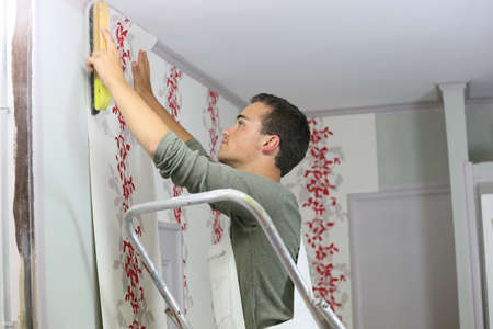 Young apprentice learning how to put wallpaper up on wall