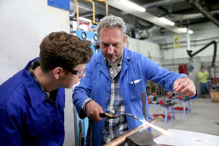 plumber: Teacher with student in metallurgy workshop