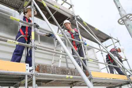 Stavební dělníci instalace lešení na místě