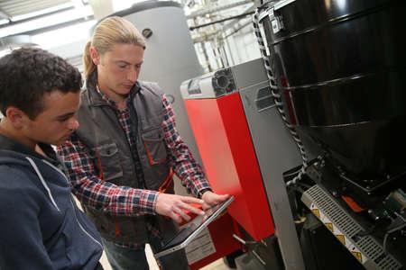 heat pump: Young man in professional training measuring heat pump temperature Stock Photo
