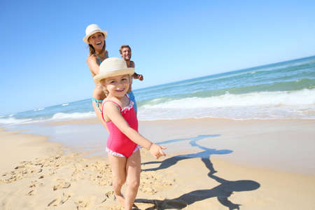 bikini couple: Portrait of little girl running on beach with parents Stock Photo