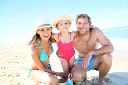 knelt: Portrait of happy family at the beach