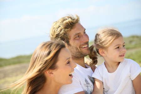 Portrait of happy family walking together in natural landscape
