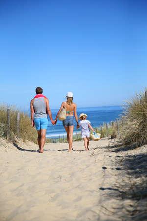 dia soleado: Vista trasera de la familia caminando a la playa en un día soleado Foto de archivo