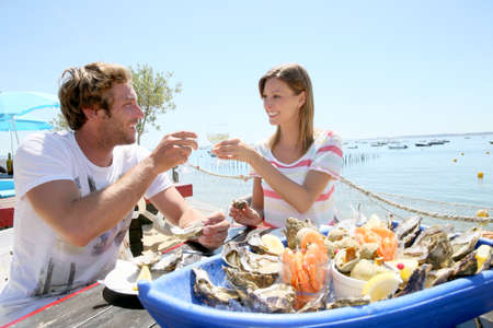 seafood platter: Couple in seafood restaurant tasting fresh oysters