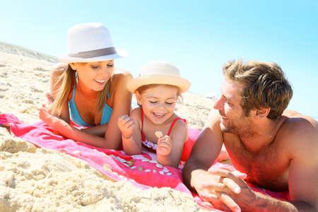 child bikini: Family playing with seashells on the beach