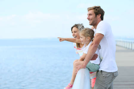Family standing on a pontoon looking at the sea