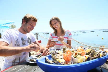 新鮮な牡蠣を味わうシーフード レストランのカップル 写真素材