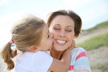 kids hugging: Portrait of cute little girl kissing her mom