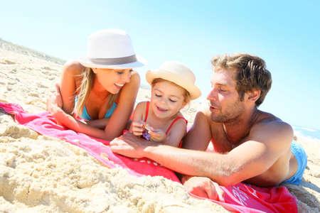 vacaciones en la playa: Familia que juega con conchas marinas en la playa