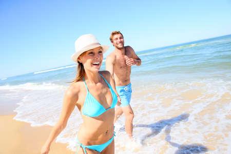 couple in summer: Couple having fun running on the beach Stock Photo