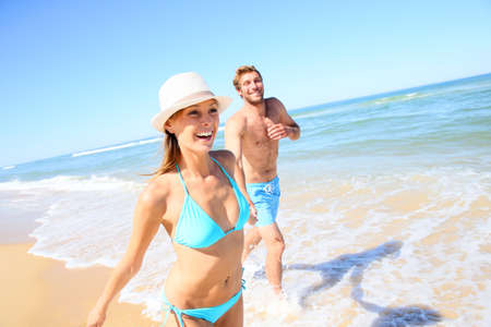 pareja casada: Junte divertirse corriendo en la playa