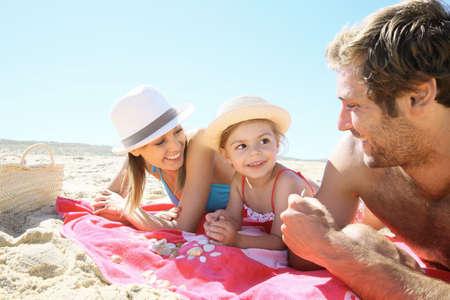 Familie, die mit Muscheln am Strand