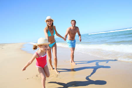 child swimsuit: Family having fun running on a sandy beach